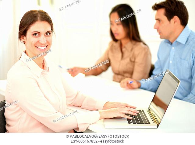 Portrait of attractive lady working on her laptop while smiling at you and sitting on office desk with coworker in background