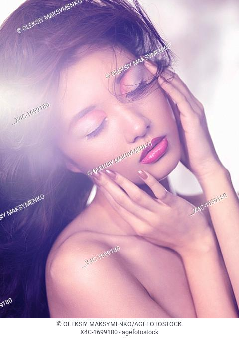 Beauty portrait of an asian woman sensual face with artistic makeup in soft light