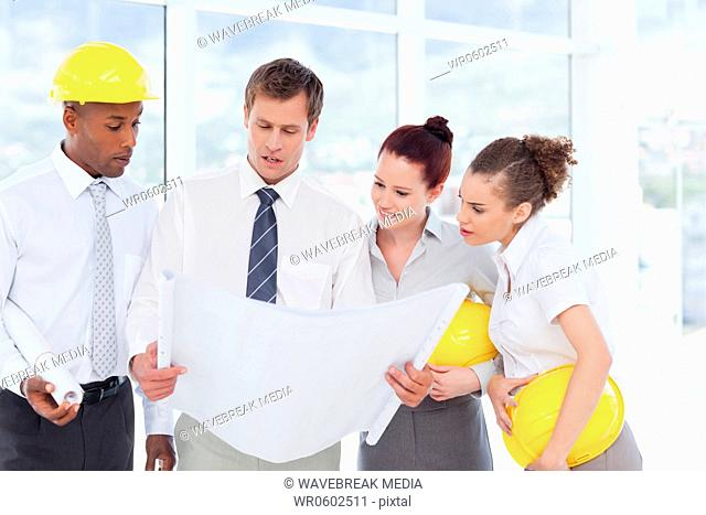 Team of architects looking at a building plan