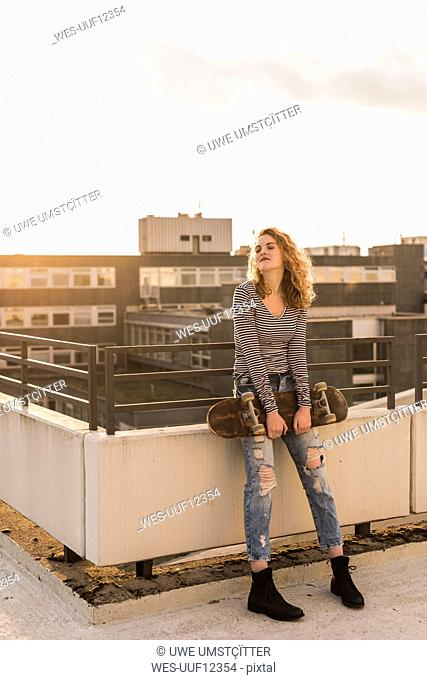 Young woman with skateboard enjoying sunset on roof terrace