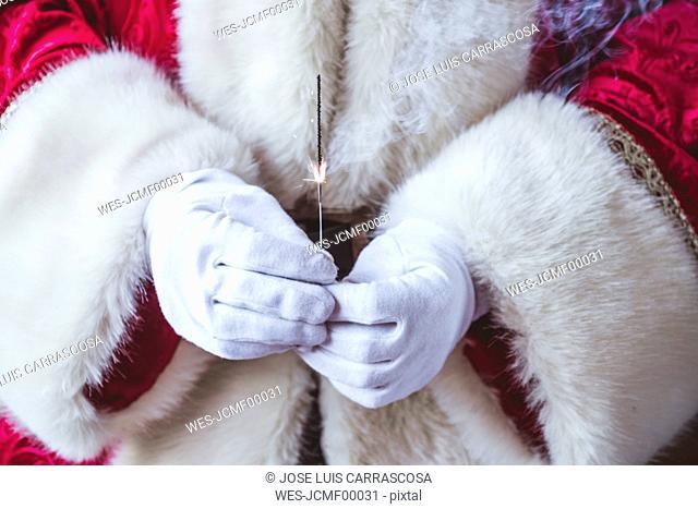 Hands of Santa Claus holding burning sparkler, close-up
