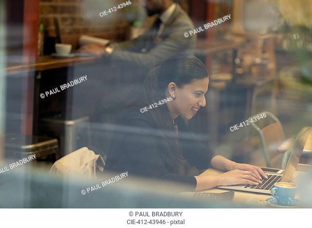 Smiling businesswoman working at laptop in cafe
