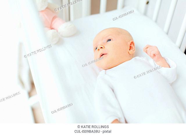 Overhead view of baby girl lying in crib