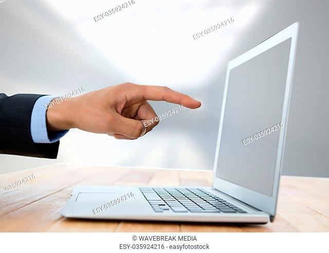 Business hand with laptop at desk with bright background
