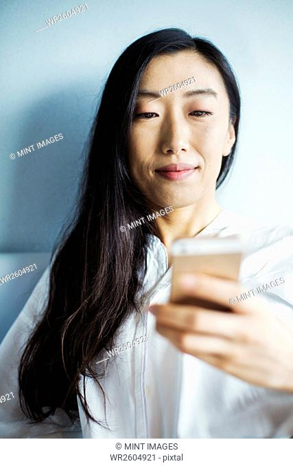 A business woman preparing for work, sitting in bed using her smart phone