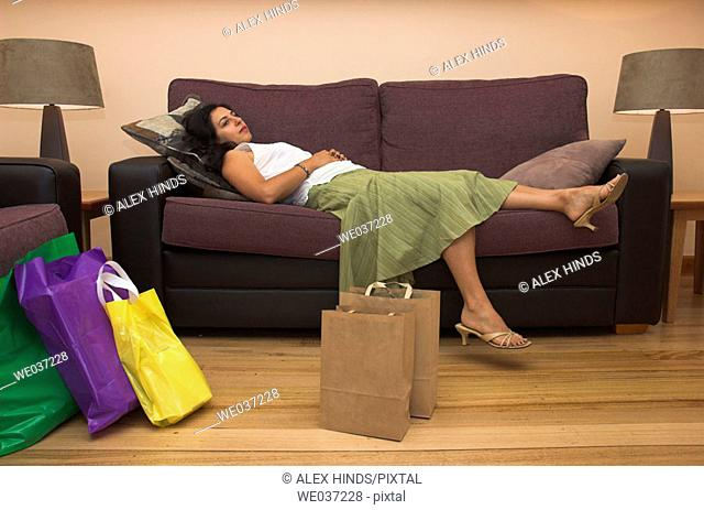 A young woman rests after a hard day shopping