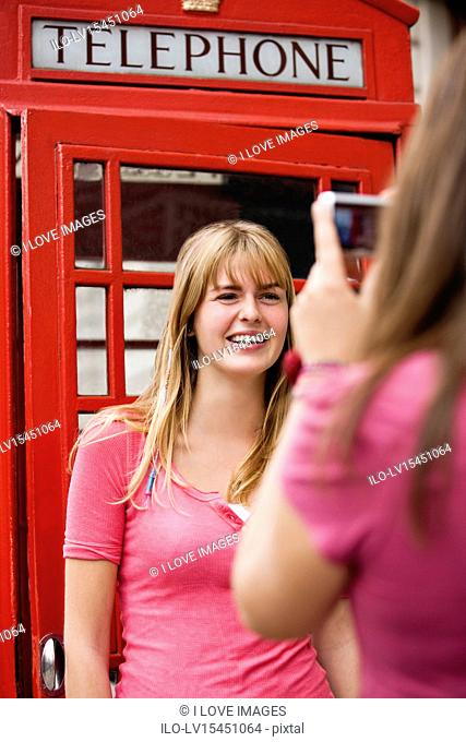 A teenage girl taking a photograph of her friend in front of a telephone box