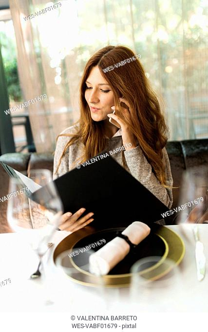 Woman sitting at table in a restaurant reading menu and talking on cell phone