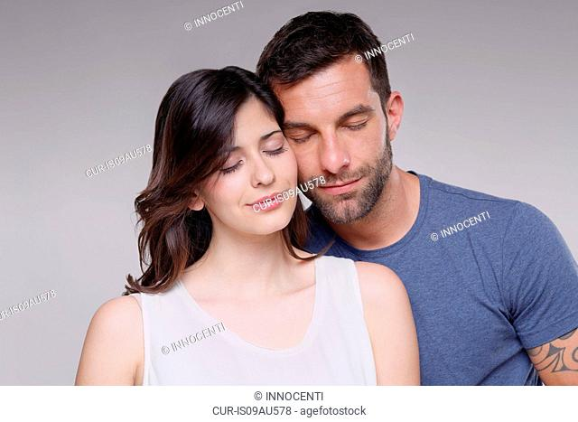 Portrait of heterosexual couple, standing together, eyes closed