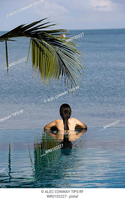 Thailand, Koh Samui. Thai Woman bathing in swimming pool next to sea