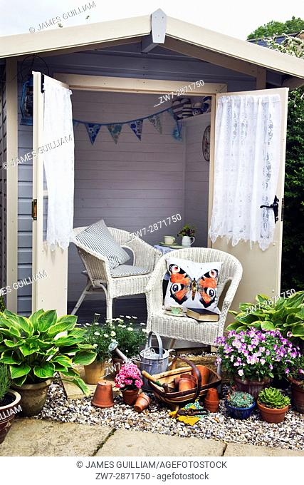 Wooden summer house with bascket chairs, garden tools and plants