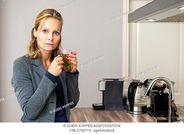 Kaatsheuvel, Netherlands. Mid adult cuacasian woman drinking tea, while standing in her kitchen