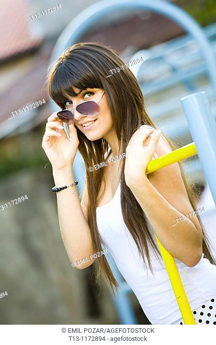 Looking over sunglasses young woman on the playground