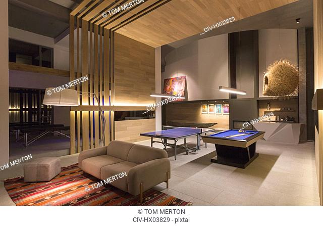 Illuminated pool table and ping pong table in modern, luxury home showcase interior game room