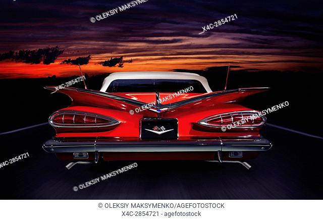 Red 1959 Chevrolet Impala Convertible classic retro car rear view on a highway in colorful red twilight nighttime outdoor scenery