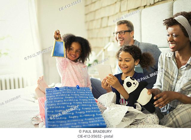 Multi-ethnic family opening birthday gift on bed