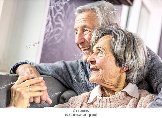 Loving senior couple sitting on sofa holding hands