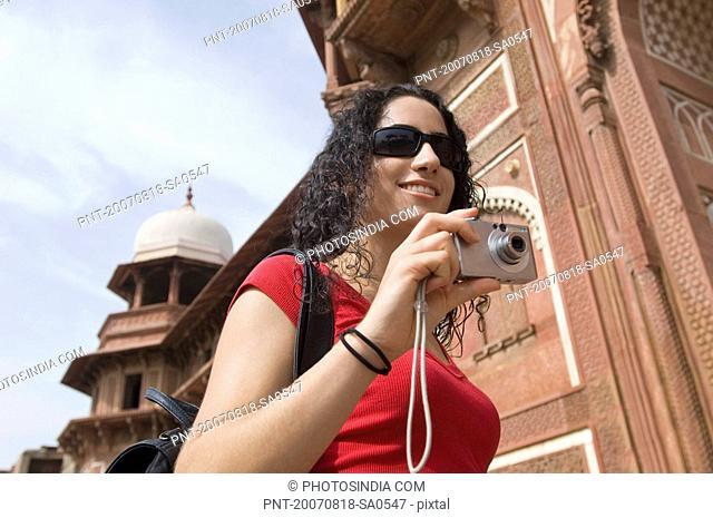 Low angle view of a young woman holding a digital camera and smiling, Taj Mahal, Agra, Uttar Pradesh, India