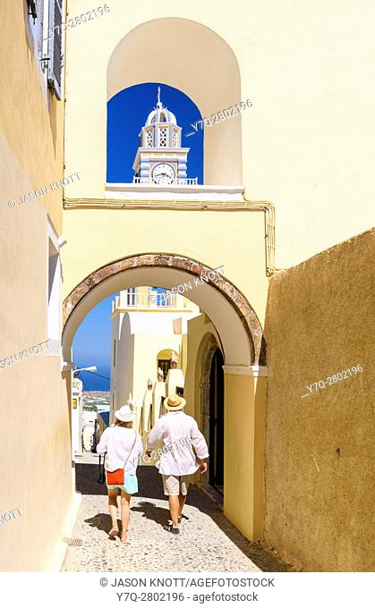 A couple walk under an archway near the St. John the Baptist Cathedral in Fira, Santorini, Cyclades, Greece