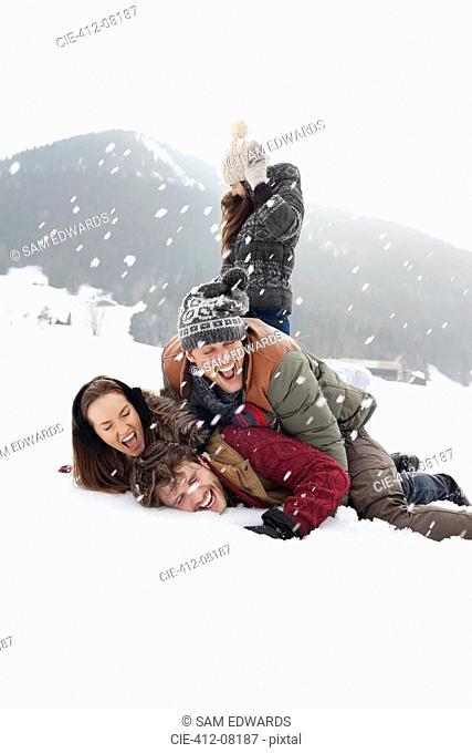 Playful friends enjoying snowball fight in field