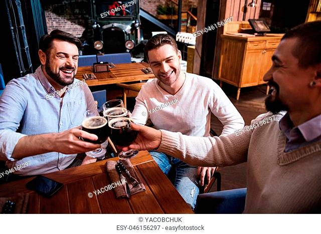 Having a great time. Happy positive handsome man sitting at the table and enjoying their drinks while having a great time together