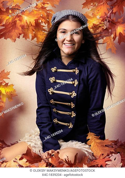 Smiling teenage girl sitting on fallen autumn leaves artistic fall fashion portrait