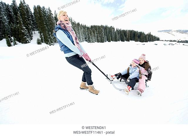 Italy, South Tyrol, Seiseralm, Woman pulling children 6-7 8-9 on sled