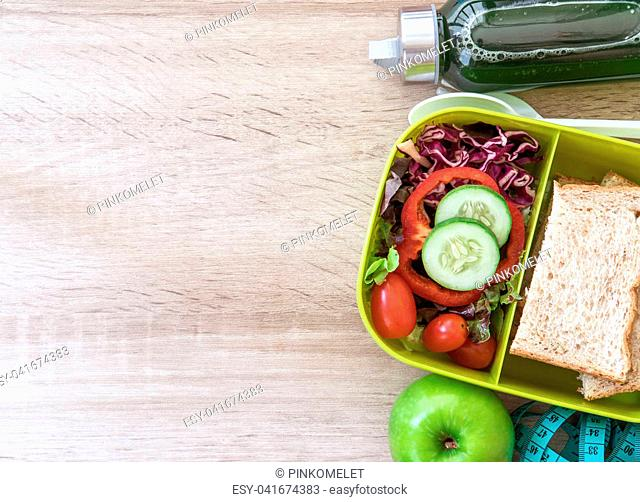 Healthy Lunch box with grain bread and green vegetable and fruit juice bottle on wooden background ,Healthy eating clean food habits for diet concept