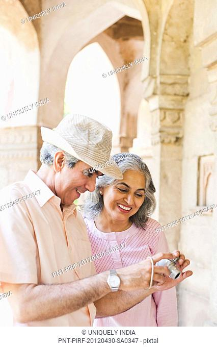 Mature couple looking photos on a digital camera, Lodi Gardens, New Delhi, India