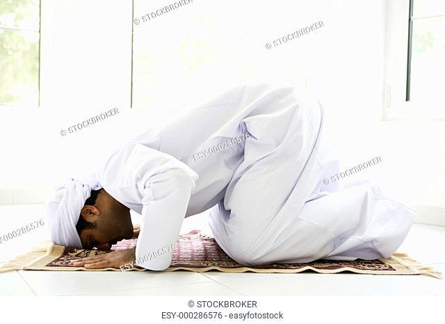 Man indoors praying on mat high key