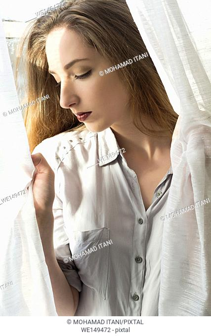 Sad woman holding the blinds looking down