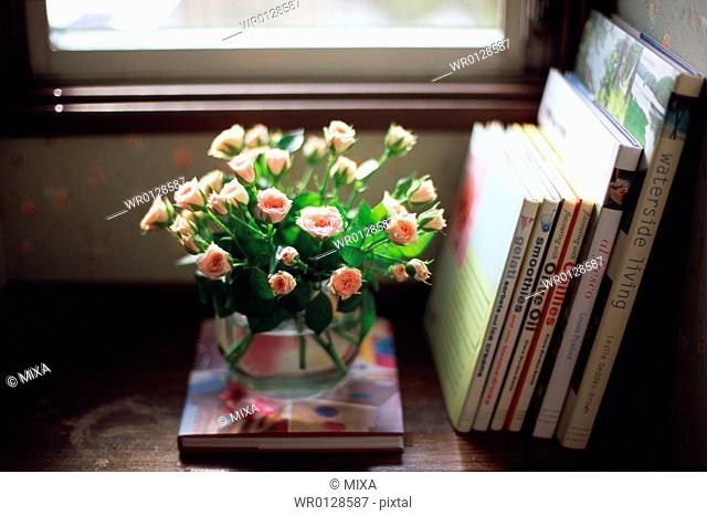 Pink roses in vase and books