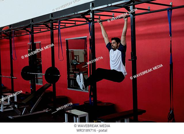 Athlete exercising on monkey bar