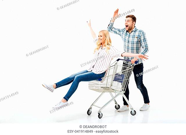 Full length portrait of a cheerful couple riding on a shopping trolley isolated over white background