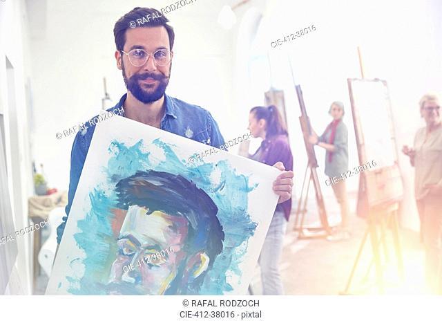 Portrait smiling, confident, proud male artist holding painting in art class studio