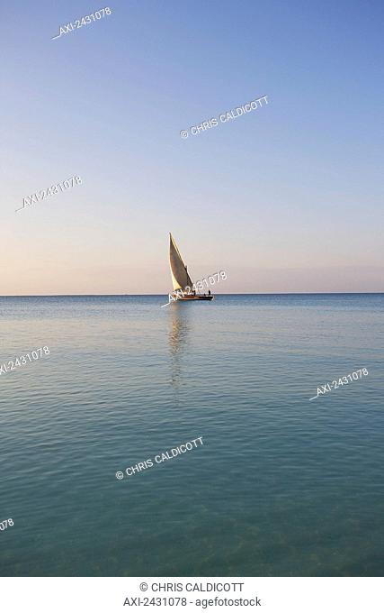 A sailboat in the distance on the tranquil water of the Indian Ocean; Vamizi Island, Mozambique