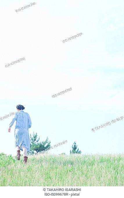Young woman walking in field, rear view
