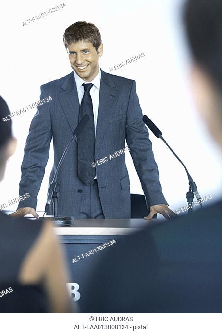 Speaker standing next to microphones during seminar