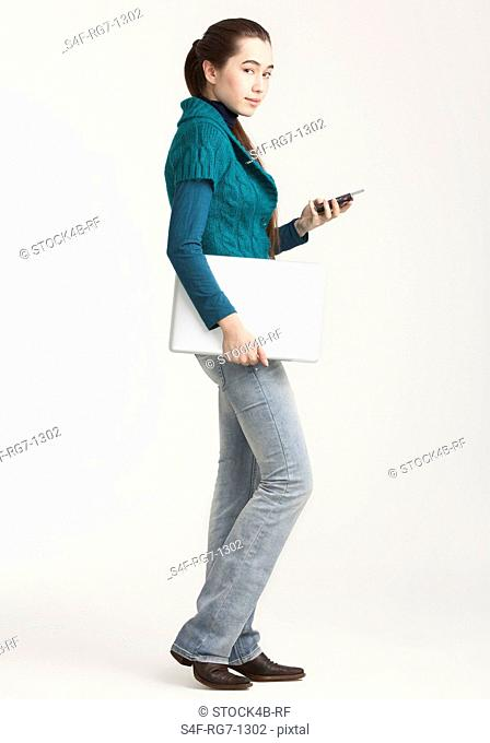 Young woman holding laptop and cell phone