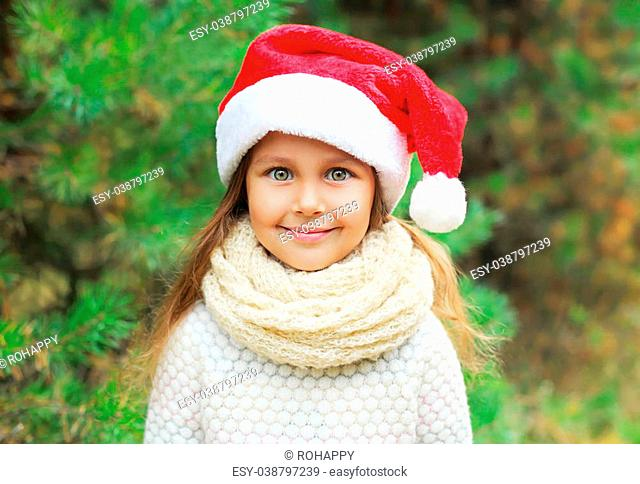 Christmas and people concept - portrait little girl child in santa red hat