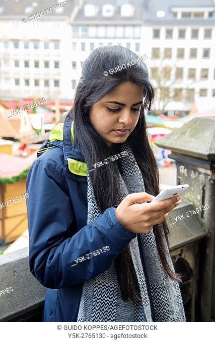 Aachen Germany. Young Indian exchange student to University of Aachen using her smarthone during a stroll down town