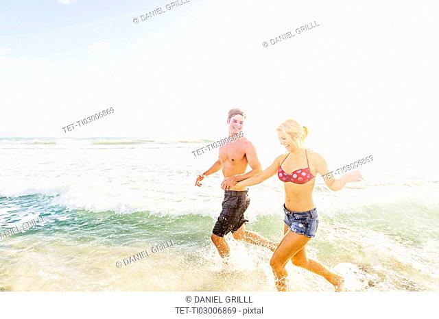 Young couple running in surf holding hands