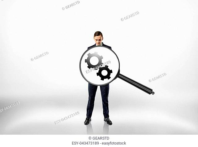 Big magnifier enlarging gear wheels inside businessman's body. Abstract process. Adjustment and regulation. Business staff