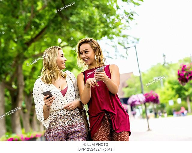Two young women walk down a path on a university campus laughing and talking together as they look at their smart phones; Edmonton, Alberta, Canada