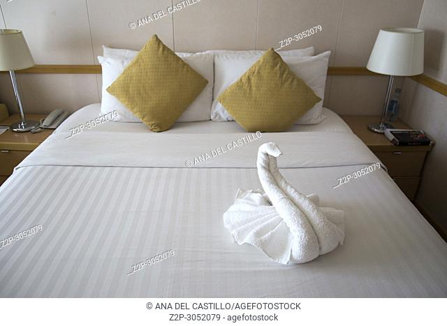 Cabin of a cruise ship with a towel swan on bed