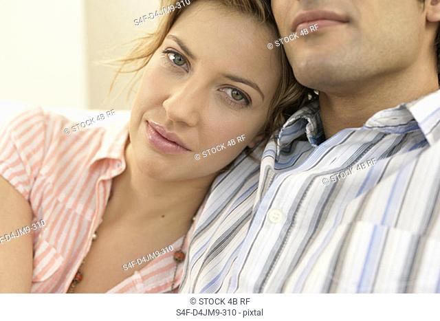Young woman resting head on man's shoulder and looking at camera