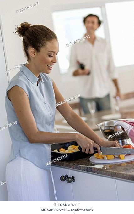 Woman is preparing vegetables on worktop in the kitchen, man is setting the table in the background