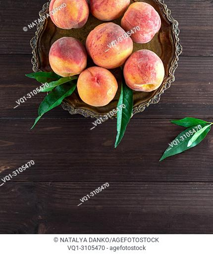 fresh ripe peaches in a round iron plate, top view, copy space