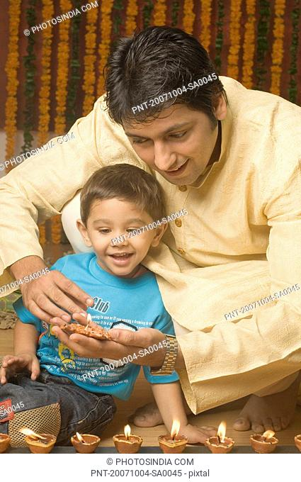 Mid adult man lighting an oil lamp with his son