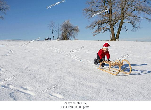 Young boy pushing sled down hill